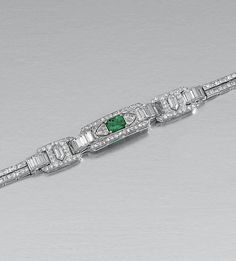 EMERALD AND DIAMOND BRACELET, 1930S.  Designed as a central plaque set with a step-cut emerald within a surround of circular- and single-cut diamonds, flanked by two similarly-set plaques, to two parallel lines of single-cut stones, length approximately 170mm