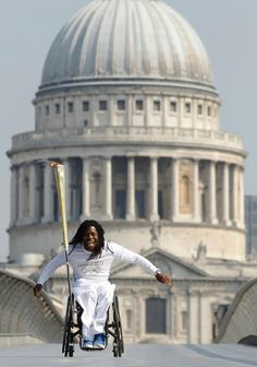 British Paralympian Ade Adepitan rolls across the Millennium Bridge in London with the Olympic Flame in tow on July 26, 2012. The London 2012 Olympic Games kick off tomorrow.
