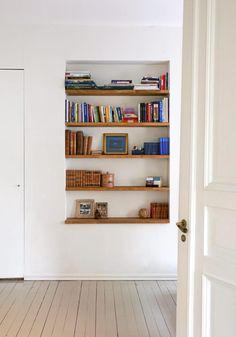 Hyllen er en innsenkning i veggen som har fått trefargede planker. Dette bryter med de hvite veggene, og sammen med de fargerike bøkene gjør det hyllen til et blikkfang.