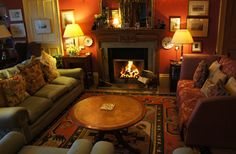 Pretty, cozy red and green room. I would have put chests or table of the same height on either side of the fireplace....the uneven height of the lamps is distracting (and one is crooked!)