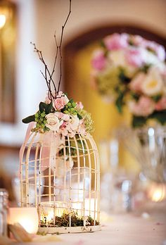 Brides.com: Brittany & Daniel in Tampa, FL. Dinner tables were decorated with centerpieces comprised of birdcages crowned with flowers and filled with moss and candles; all floral design was by The Wedding & Event Studio.