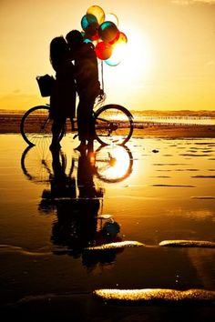 a boy and a bike with balloons on the beach? what are they doing? trying to alliterate?