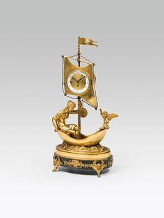 """Empire-Uhr, Sebastian Gurowsky, Wien, 1. Viertel 19. Jh. Bronze, feuervergoldet, Sockel dunkel patiniert; fein ziselierte & vergoldete Bronzeapplikationen; auf einem ovalen Sockel mit plastischen Meereswogen steht ein kleines Segelboot mit Dame & Putto, am Schiffsmast ist das Uhrwerk befestigt; gouillochiertes Bronzezifferblatt mit Emailziffernring, signiert: """"SEBA. GUROWSKY IN WIEN"""" (auch Sebastian Gurewsky, Wien, 1816-1843) feines Wiener Werk mit Viertelstundenschlag auf Glocken…"""