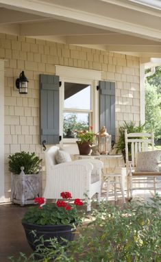 cozy cottage style back porch red geraniums and blue shutters