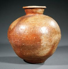 A Japanese Shigaraki Pottery Jar probably Edo Period (1603-1868), tapered bulbous body with flared neck and everted rim, height 15 in
