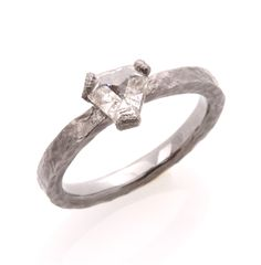 2mm 14k white gold rustic hammered shank with a single 0.77ct inverted triangular step cut diamond set at top. The entire ring has been darkened with black ruthenium.