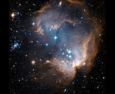 Star Cluster NGC 602  Newly formed stars carve a cavity in the center of a star-forming region of the Small Magellanic Cloud.