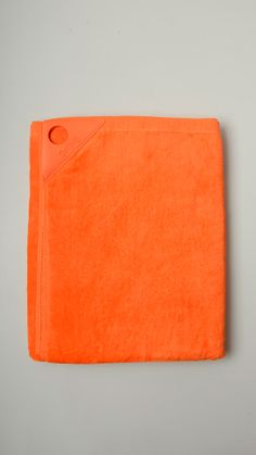 Plain orange terry cotton fabric featuring rubber label, 35'' x 57'', 100% cotton.