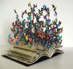 Could be MINIATURE !.......  3D book with multi-colored butterflies coming out from the pages - or BATS or other SPOOKY  things in a Wizard's room..?