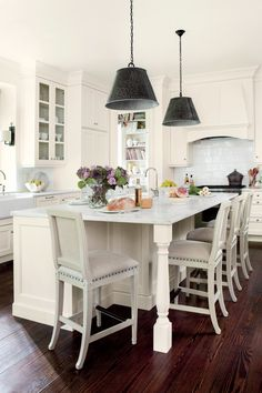Designer Suzanne Kasler rescues a dark and dated Atlanta kitchen with a timeless white palette and her signature inviting style. The walls, trim, cabinetry, and ceiling are all painted Benjamin Moore's Linen White in the same eggshell finish. Meanwhile, hammered metal pendant lights and newly refinished wood floors are a nice counterpoint to the mainly white space.  See more of the Lighten Up Kitchen Update