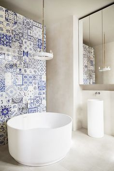 Contemporary bathroom with blue and white tiled accent wall, round bathtub and unique, modern chandelier.