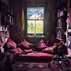 Gypsy bohemian hippie bedroom or nook in reds and purple with ethnic tribal prints and oversized pillows