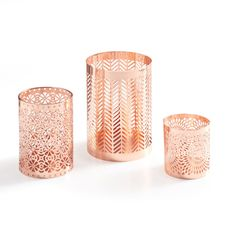 Fine ornamental work defines Danya B Set of Rose Gold Filigree Hurricanes. Each piece has a different filigree pattern in rose gold tone that when placed on a table or shelf will add a touch of on trend metallics to your home decor, wedding or party