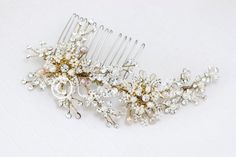 This side bridal comb is a detailed design of wired leaves beaded with ivory pearls and crystal beads woven with rhinestone accented silver wire. The center is a cluster of larger round rhinestone jew