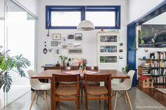 Sala de jantar tem parede galeria, mesa e armário de madeira.