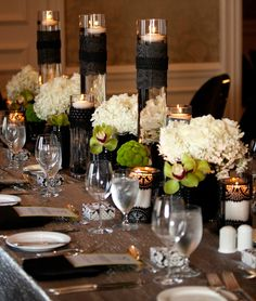 Beautiful black and white centerpieces- black lace, white hydrangeas, roses, baby's breath, with pops of green orchids!