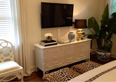 Luxe Report - bedrooms - leopard ottomans, leopard print stools, leopard print ottomans, bamboo dresser, white bamboo dresser, faux bamboo dresser, tv across from bed, bedroom tv, gold faceted lamp,