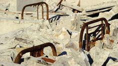 Respaldos de sillas totalmente oxidadasasoman de entre los escombros de un edificio