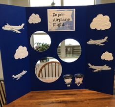 Paper airplane toss game for carnival, festival, birthday party  Supplies: blue trifold board, planes, clouds and cartoon pilot kids from google.  Title created in Project Life app.