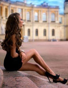 Leggy brunette in a little black dress and peep toe platform heels taking a break in the courtyard