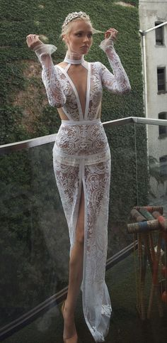 Lior Charchy 2017 Wedding Dress. Although it has a high collar and long sleeves, this gown still has too much flesh showing to be worn in church. You've got cleavage down to the navel, bare flanks and a slit up the middle of the skirt right up to the crotch. And the whole dress is lace embroidered onto illusion, so it's all transparent. As pretty as this looks here, it's too many places uncovered. Can't see the back here but I expect it's also bare. Sew the slit to the knee at least.