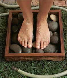 The box shown is 16 inches square. Fill it will several layers of smooth, flat stones - river stones look particularly handsome and are easy on the soles. Sand rinses away into the stones and grass below, leaving bare feet clean.