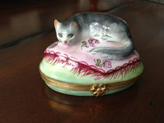 What an adorable and spectacular vintage Limoges box this is! Entirely painted by hand, theres a beautiful dark gray cat perched atop a very french looking lilac colored tapestry atop a celadon green base. Inside there is an adorable mouse painted as if it is running across. Excellent vintage condition.    Would make an amazing addition to an existing collection, or spectacular mothers day gift for your cat loving mom ; ).    The Limoges Box is a small hinged porcelain trinket box produced…