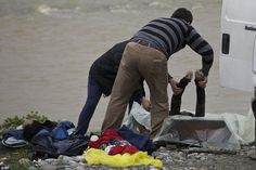 Macedonian coroners place the body of drowned migrant in a coffin on the river bank of Suv...