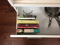 Cookbooks in a pots and pans drawer using an ikea VARIERA pot kid organizer.