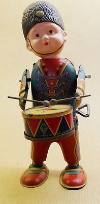 Soldier playing Drum. With fixed key and a celluloid head. In very good condition and working order. Just a little playwear on both arms. Hight is 15 cm.    Shipping Costs:    To The Netherlands:   $ 11.00  E. U.  Countries:          $ 20.00  Outside E. U.               $ 34.00    Please feel free to visit my eBay Store for more antique and vintage tin toys and Scuco Dance Figures.