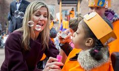 Bubbles for the Queen! A Dutch schoolgirl blew bubbles as Maxima watched during the King's Games (Koningsspelen) in Amsterdam.