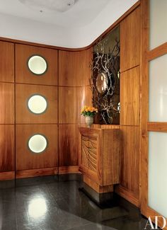 In the entrance hall, an Hervé Van der Straeten mirror from Ralph Pucci International is mounted over a Wendell Castle cabinet; both pieces were custom made   archdigest.com