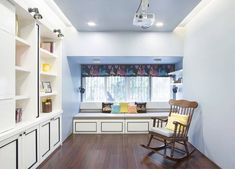 A Room with Wooden Flooring comprises of Cushioned Wooden Seating with Storage below in front of Window with Roman Shades, Wall ✨ Storage Unit with Display Boxes & a Wooden Rocking 🪑 Chair in Front! - GharPedia Wall Storage, Storage Units, Wooden Rocking Chairs, Display Boxes, Wooden Flooring, The Unit, House Design, Windows, Table