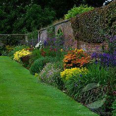Herbaceous summer border of anthemis, achillea, Verbena bonariensis, phlox, golden rod, hardy geranium, dahlia, red hot poker, salvia and delphinium. Pool garden. England, Middle Claydon. Bucks.