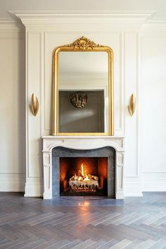 Luxurious French fireplace design displaying a gold ornate mirror flanked by gold sconces over a white mantel. Custom Fireplace, Home Fireplace, Modern Fireplace, Fireplace Design, Fireplace Mantels, Mantles, Above Fireplace Ideas, Mirror Above Fireplace, Fireplace Surrounds