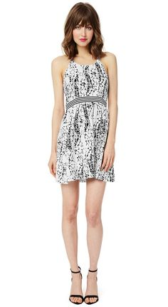 A splatter of black paint adds a stunning contrast effect to a flirty mini dress for a number that's both feminine and edgy. Delicate shoulder...