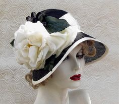Black straw hat with cream colored flower and trim.