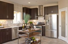A stainless steel range hood and appliances define this contemporary kitchen. Plan 2, a new home built by Centex Homes at Spectrum. Elk Grove, CA.