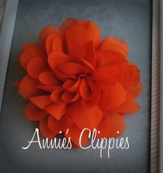 4 Petal Flower Clip: Orange    This orange petal flower is made of chiffon and measures approximately 4 inches across. It is attached to a