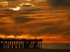Unusual layers of clouds diffuse the sunlight at the end of a winter day in Hermosa Beach, California.