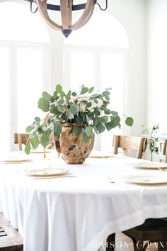 Love the wood vase! white roses and eucalyptus centerpiece make a gorgeous, simple spring table - perfect for Easter, Valentines Day, or any celebration #eastertable #springtable #tablescape #eucalyptus #centerpiece #vintagechina #goldflatware #easterdecor