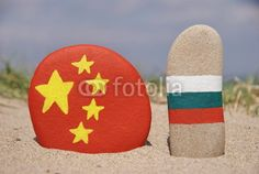 China and Bulgaria's flags on stones with sand background