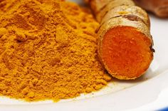 A spoonful of turmeric powder in a wooden spoon, they are tiny grains that look reddish yellow in color