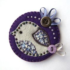 This is a lovely handmade fabric brooch. It features a little felt bird with appliqued wing and belly in lovely Liberty print fabric. It is mounted onto a circular purple felt base and is edged with pretty coordinating beading and a ribbon tail. Gold Fabric, Fabric Art, Fabric Crafts, Sewing Crafts, Fabric Brooch, Felt Brooch, Bird Applique, Wool Applique, Felt Embroidery
