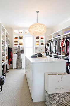 The master bedroom suite includes this expansive walk-in closet that features dressers, hanging rods and customized shelves for shoes, bags and more.