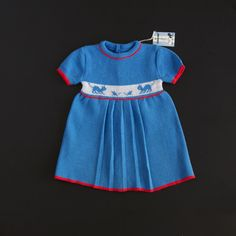 "Lovely blue knitted dress with red accents and an adorable little cat and mouse scene on the chest.Fastens with two little buttons up the back.This dress is new and unworn. It comes in an excellent vintage condition.Brand: Rhone Poulenc Textile - made in FranceFabric: AcrylicSize: 6 months size 67. This seems accurate.To ensure a proper fit please check measurements taken below.Shoulder to Hem: 38cm (15"")Shoulder to shoulder: 21cm (8,5"")Armpit..."