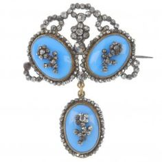 A late Georgian cut steel and paste brooch, circa 1820, the oval blue glass cabochon, with cut-steel floral centre and surround, suspended from a similarly-set surmount panel. Length 4.6cms.