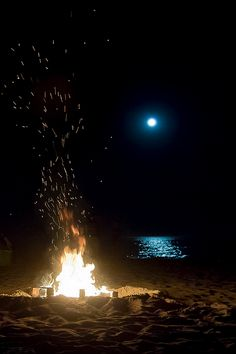 A picture of a bonfire on the beach at night and the moon's reflection in the water.