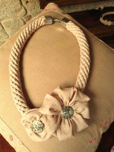 Collar largo de cordón en rosa palo con motivos florales, apliques y cierre metálico en color plata