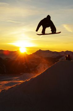 #Snowboard at #Sunset Snowboard at sunset jumping over the sun setting behind the mountains.